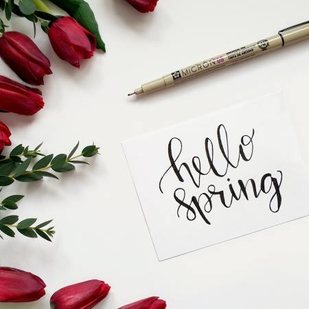 red flowers and a piece of paper with hello spring and a pen